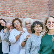 Mehrere Frauen im höheren Alter und eine junge Frau lächeln in die Kamera.